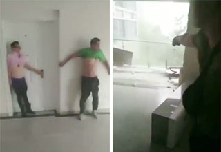 two guys holding the wall in their blown open apartment