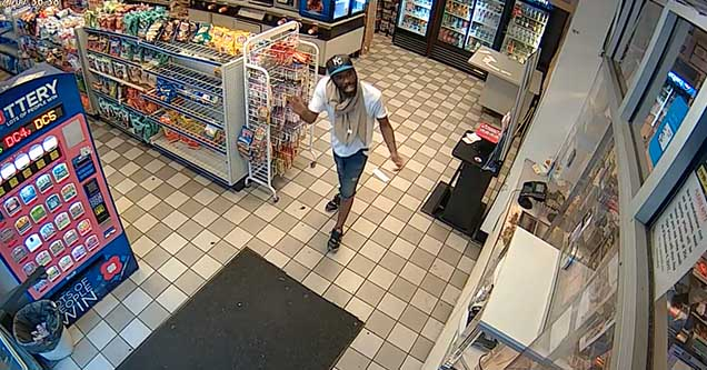 A man attempting to steal goods is walking towards the front door of a convenience store in 2018.