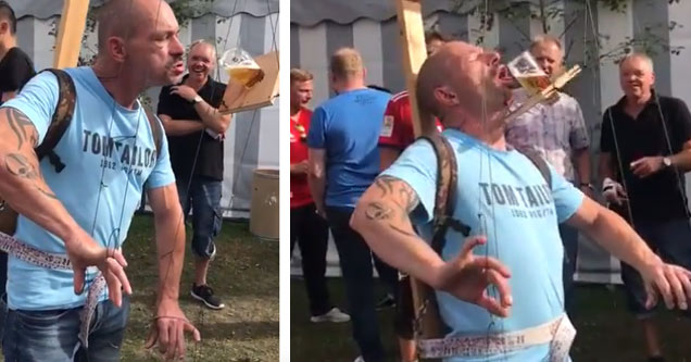 a man in a blue shirt wearing a marionette styled contraption with strings attached to his fingers to pour a beer into his mouth
