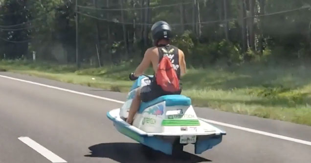 A man rides a Jet Ski down the road in Florida in 2018.