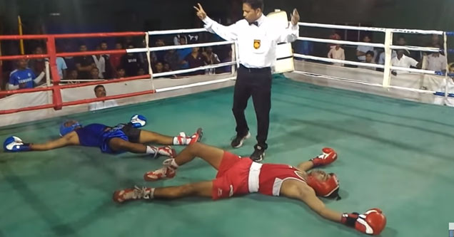 two boxers one in red and one in blue laying on the mat after a double knockout as the referee counts them out
