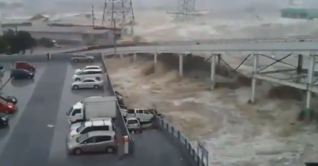 a parking garage in Japan with a massive Tsunami rushing in