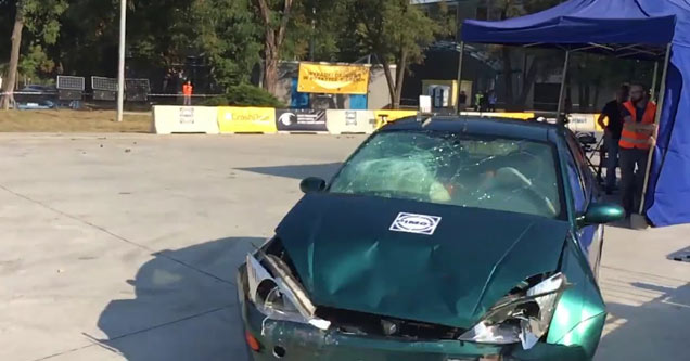 a blue car with a smashed hood and busted windshield during a crash test
