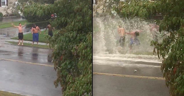 Three guys stand on the side of a road as cars drive by, splashing them with water from the rainy road.
