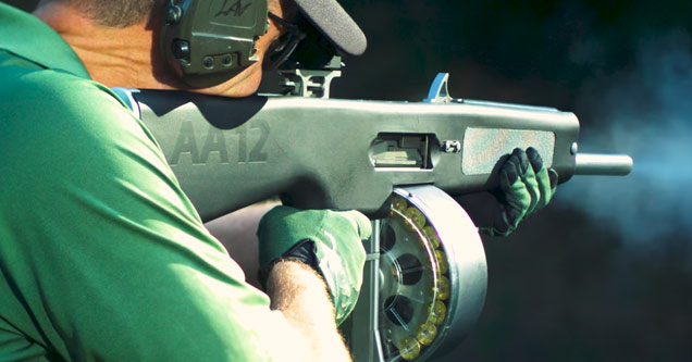 a man in a green shirt and gloves holding a fully automatic shotgun