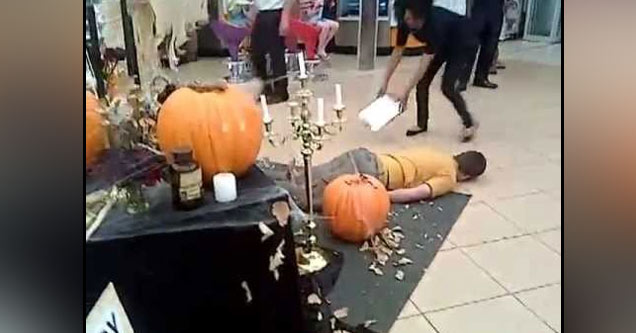a man wearing an orange shirt and gray pants lays on the ground pretending to have a seizure after getting scared