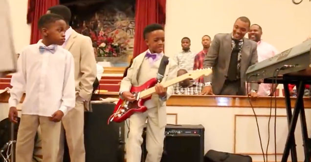 10 year old boy in a tan suit playing a red Stratocaster guitar at his church