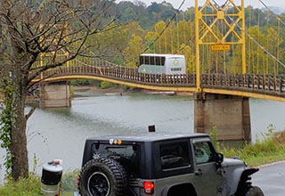 A bus is driving over a historic suspension bridge in Beaver, Arkansas.