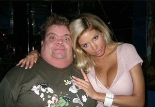a nerdy heavy set man with a hot busty blonde woman
