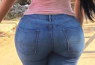 a girl with a big butt wearing blue jeans and a pink shirt