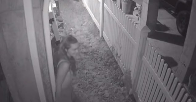 black and white home security footage of a woman leaning up against a mans wall to pee and getting sprayed by a sprinkler