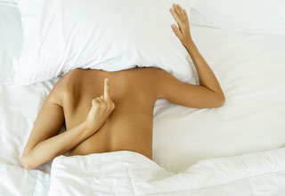 Woman laying in bed with finger behind her back