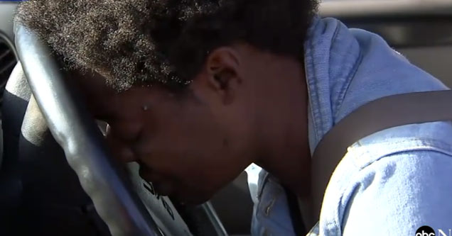 a black woman who is the mother a student at the school where a stabbing took place rests her head on the steering wheel of her car in shock and disbelief