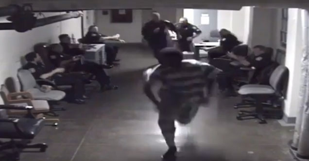 a prisoner in black and white uniform runs down a hallway with police officers sitting on either side of him