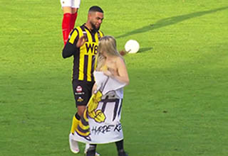 a lady on the field in the netherlands without any clothes on, a player is staring at her