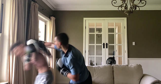 Two guys wearing boxing gloves are sparring in a living room in October 2018.