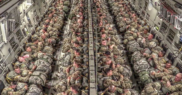 a large military plane full of paratroopers in military uniforms waiting to jump out of the plane