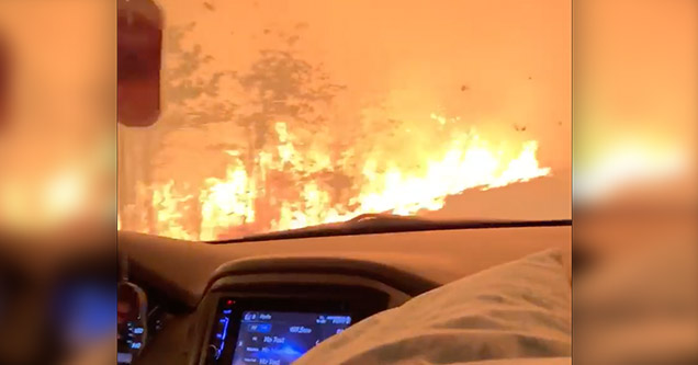 A family drives through the 'Camp Fire' that is raging in Paradise, California in November 2018.