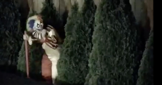 A creepy looking clown is peeking out of some bushes as seen on a security camera in Everett, Washington in October 2018.