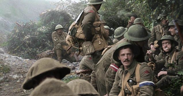 a wwi soldier amongst his comrades looking toward the camera