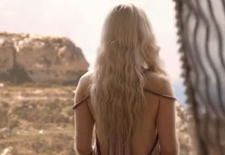 daenerys targaryen stands looking out of the window over the landscape