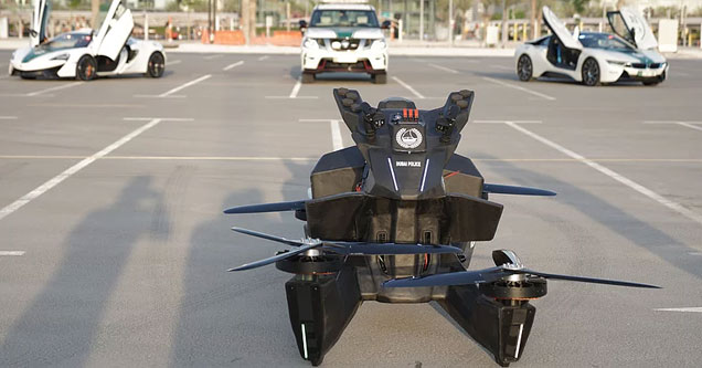 a hoverbike flyable drone with several of dubais sports car police cruisers behind it