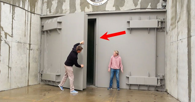 a man in a black shirt and tan pants opens the giant metal door to a missile silo and a young boy in bluejeans and pink hoodies stands watching him