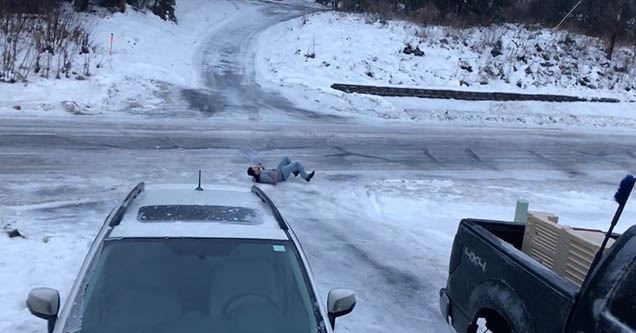 A man is lying on his back after falling and sliding down his driveway in Palmer, Alaska in 2018.