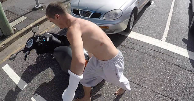 A young man is dragging another guy's scooter across the road during a road rage incident in Australia in 2018.