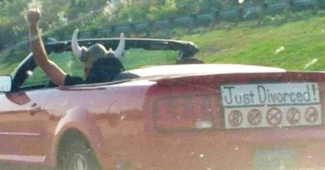Man in a viking hat driving with a 'Just Divorced' sign on the back