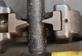 a hydraulic cutter trying to cut through a metal pole