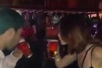 A guy drinks with an irish girl.