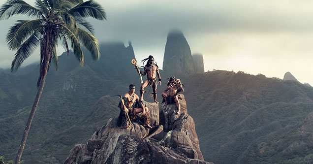 A group of tribal men sit atop a mountain.
