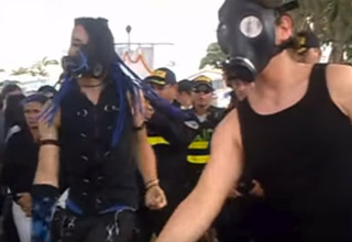 two men wearing gas masks and cyber goth clothing are dancing at a funeral in front of a crowd