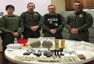 a group of texas police officers posing behind a table full of drugs and contraband and money