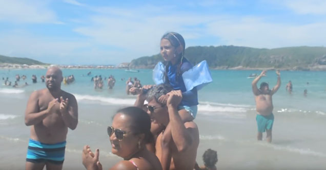 Lost little girl on Brazilian beach surrounded by people clapping