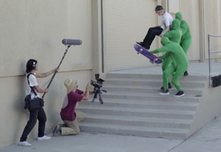 Three men in chroma key suits helping skateboarder Jeff Won Song pretend to skateboard