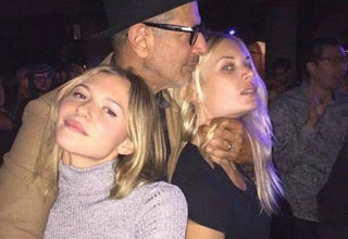 actor jeff goldblum with two young hot girls and his hands around one of their necks