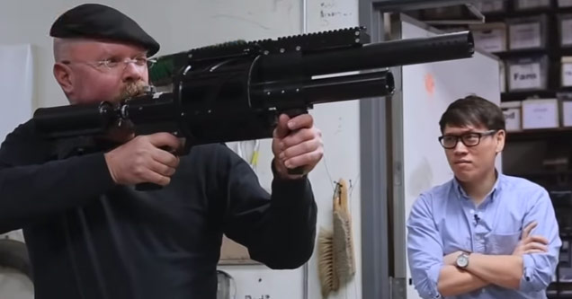 actor and inventor jamie hyneman holding a large black grenade launcher as a man in glasses with his arms folded watches