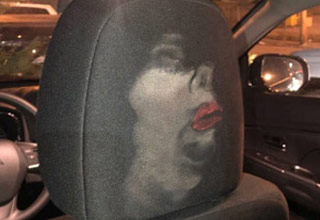 the back of a drivers seat with an image of a face that slammed into it with a lot of makeup on