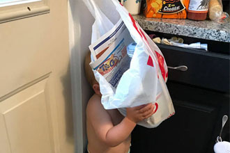 A cute kid hiding behind a bag.