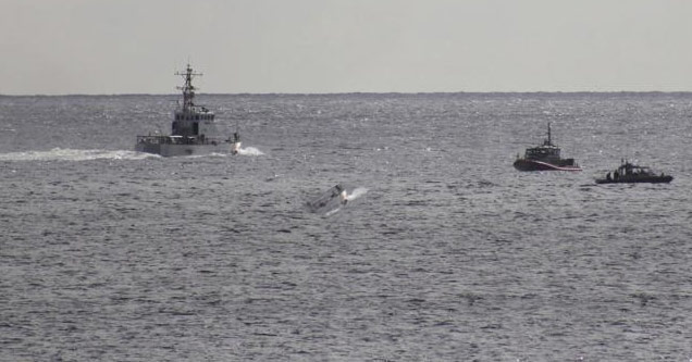 a photo of the ocean with a large coast guard ship and two smaller ones next to a crashed vintage fighter jet