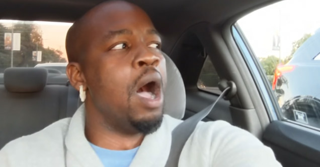a black man wearing a blue shirt is singing in the car