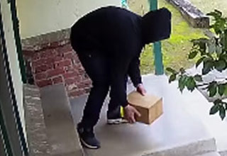 a man wearing all black bends over and steals a package off a porch
