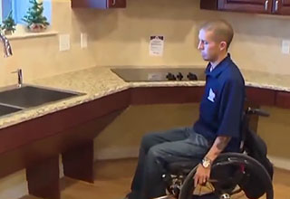 a man in a wheel chair inside of a new home's kitchen