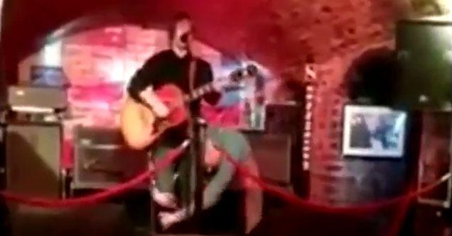 a man playing guitar in a dimly lit bar