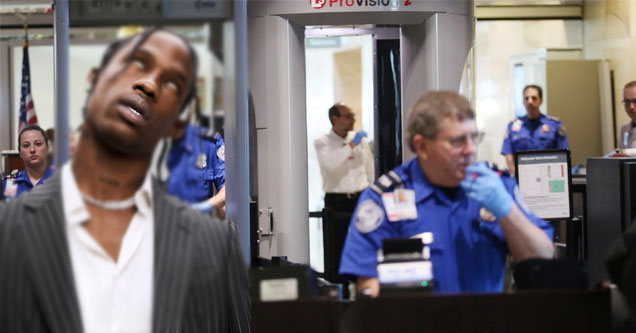 travis scott rolling his eyes in front of a tsa stand