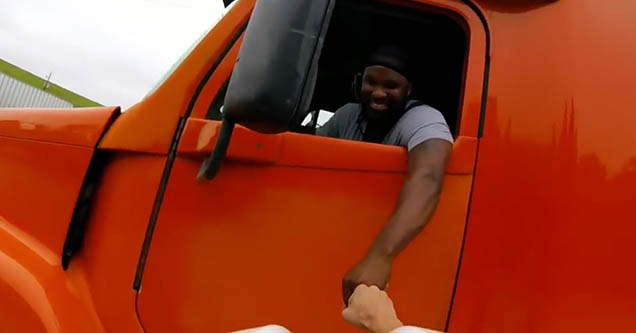 A man driving a red semi-truck fist-bumps with a cyclist that he nearly hit while driving down a road in Savannah, Georgia in 2019.