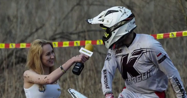 a lady holding her mic up to a man on a dirt bike