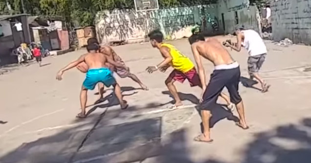 a group of guys playing a game of pickup basketball on an outdoor court